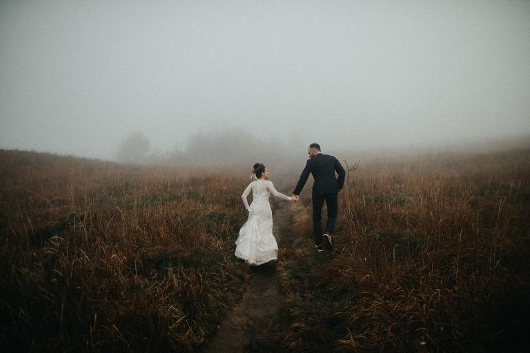 para podczas sesji ślubnej w Bieszczadach wchodząca pod górę we mgle