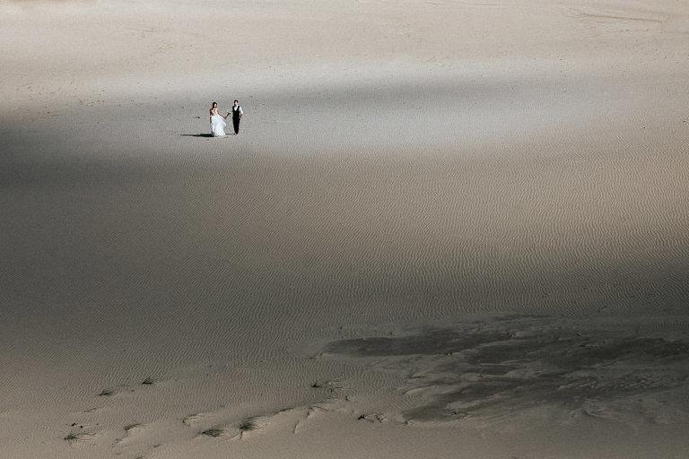 para spacerująca po pustyni sesja ślubna w Łebie