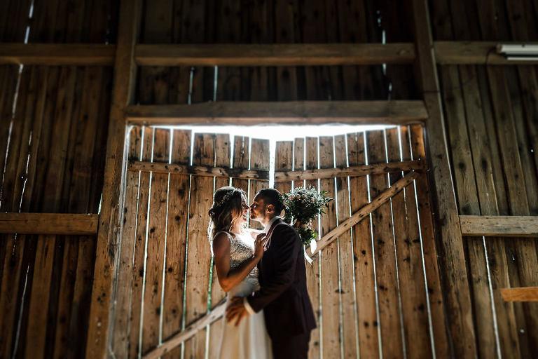wesele w stodole nowe kawkowo para pozująca na tle starych drzwi stodoły